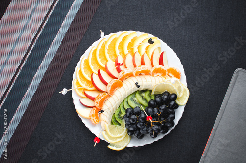 on a black background in a white plate fruit slicing, beautifully laid out