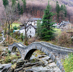 view of the old Roman stone bridge with two arches near the village of Lavertezzo in the Swiss Alps