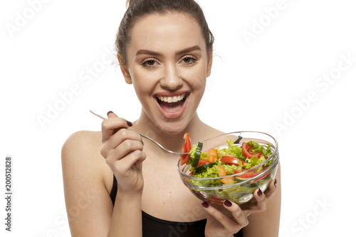Young beautiful woman eating salad on white background