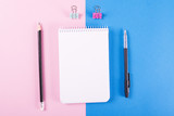 Note book next to pencil, ballpoint pen and colorful clips on pink and blue background. Mockup. - 200517620