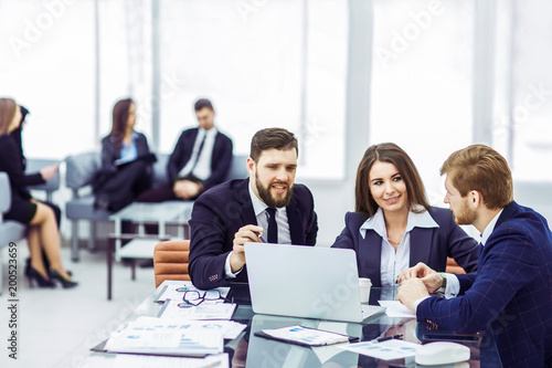 employees of the company work on laptop with information on the development of the company