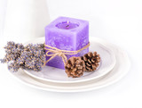 Still life with lavender candle, fir cones and dry lavender on a white plate on white background.