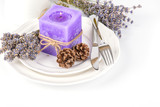 Still life with lavender candle, fir cones and dry lavender on a white plate on white background