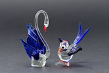 Two glass bird ornaments, made with clear, blue and red glass photographed against a black background - 200536886