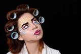 Model with pop art makeup against black background.