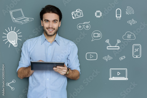 Skilled manager. Cheerful clever professional manager standing with a convenient tablet in his hand and smiling happily