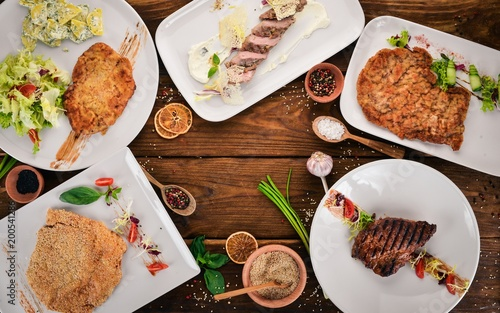 Fotobehang Steakhouse A selection of juicy steaks and schnitzels. Meat. Top view. On a wooden background. Copy space.