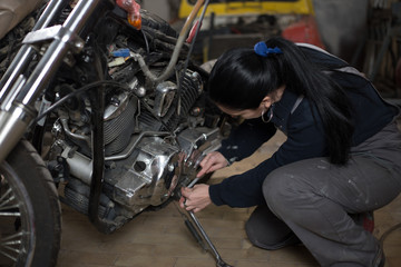 Girl worker in motorcycle repair shop