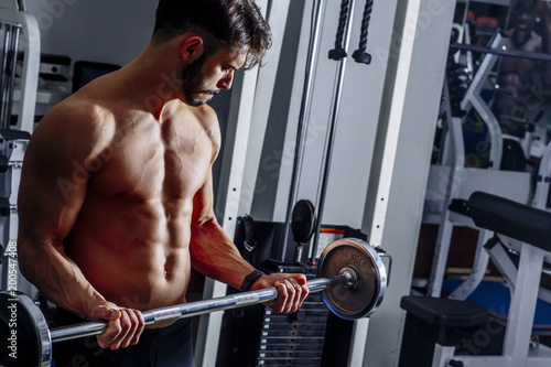 Poster Portrait of young man flexing muscles with barbell in gym