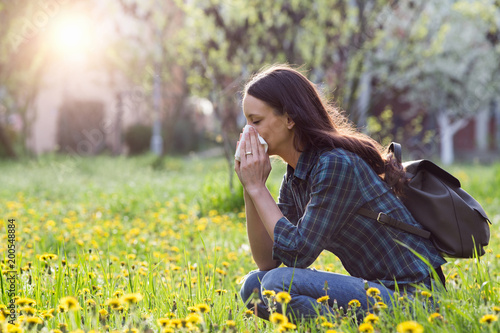 Woman blowing nose because of spring pollen allergy - 200548884