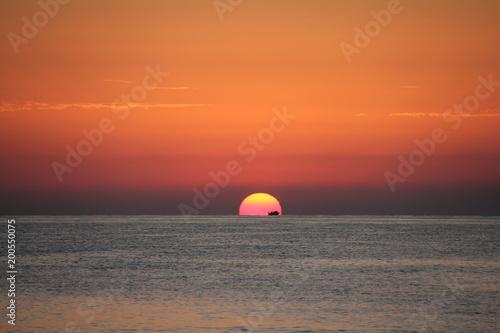 In de dag Ochtendgloren Sunrise in the sea with a cargo boat