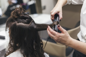 Hairdresser woman uses the straightener for styling of his young client in the salon