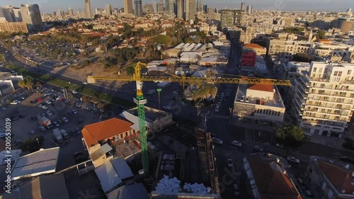 Drone footage flying over Tel Aviv in the evening while focusing and tilting down to focus on an industrial construction crane in the middle of the city