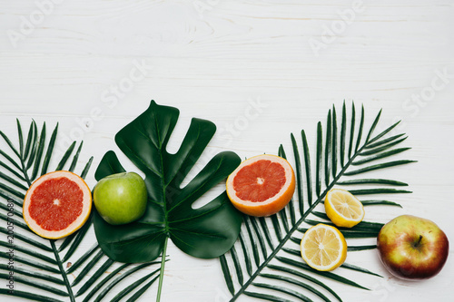 Foto Murales Composition with tropical leaves and frech fruits on light background