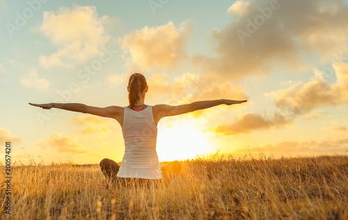 Leinwanddruck Bild Female doing stretching exercise in a open field.