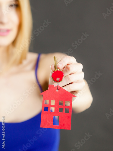 Woman holding key with house symbol