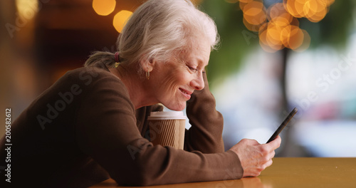 Happy elderly white woman using mobile device sitting outside at coffee shop