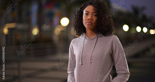 Tough African woman in gray hoodie looking at camera in street at night