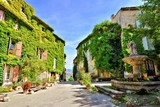 Leafy town square with fountain in a beautiful village of Saignon, Provence, France