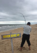 Never Give Up sign on beach background with struggling fisherman