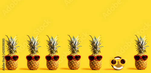 Leinwanddruck Bild Series of pineapples and a coconut wearing sunglasses on a yellow background