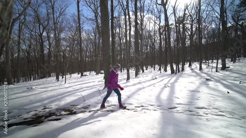 Wide tracking clip of pretty, mature woman hiking in a snowy forest on a sunny winter day.