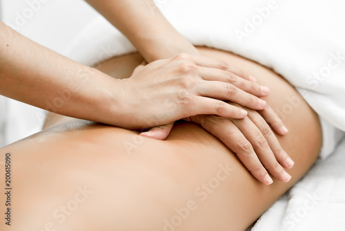 Young woman receiving a back massage in a spa center. © javiindy