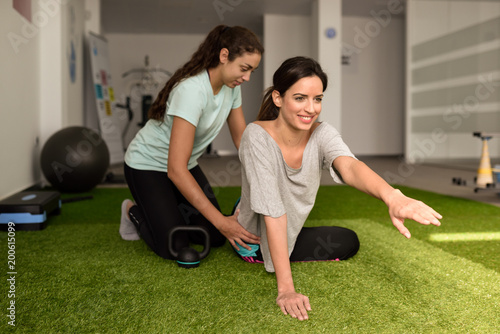Physical therapist assisting young caucasian woman with exercise - 200615099