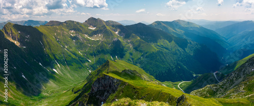 Plexiglas Nachtblauw panorama of Fagarasan mountain ridge in summertime. lovely landscape with cliffs and grassy hills over the valley. TransFagarasan road in the left corner runs through the valley in to the distance