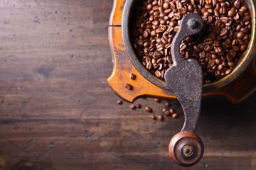 Old coffee grinder and roasted coffee beans.