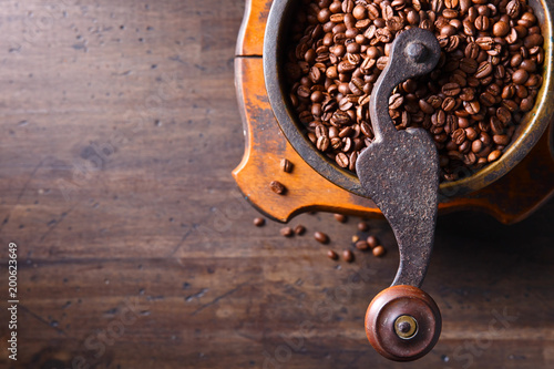 Old coffee grinder and roasted coffee beans. - 200623649