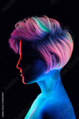 Model young beautiful girl portrait in studio, makeup, neon colors, ultraviolet lamp, color make-up, creative. Glows in the dark. Hair coloring with neon paints. Body art is blue, green, orange. - 200629827