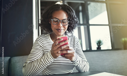 Smiling young African woman reading text messages in a cafe