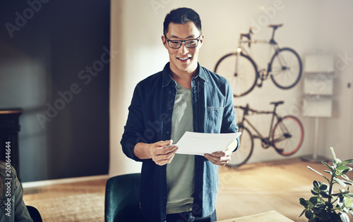 Smiling Asian man standing in an office giving a presentation