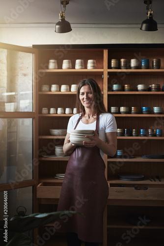 Foto Murales Smiling artisan standing in her pottery studio holding ceramic plates