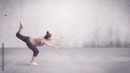 A beautiful young hip hop dancer dancing contemporary urban street dance in empty clear grey wall background concept. - 200646425