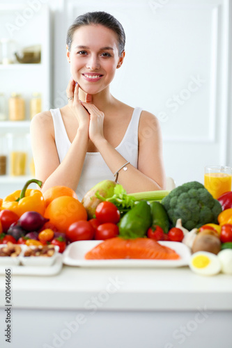 Young and cute woman sitting at the table full of fruits and vegetables in the wooden interior