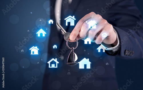 Businessman in suit holding keys with house graphics around and dark background  - 200647860