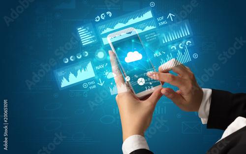 Żeńska ręka używać smartphone z pieniężnym tropi pojęciem ilustrującym wykresami i symbolami