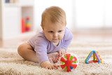 Baby girl playing with colorful toys sitting on a carpet at home