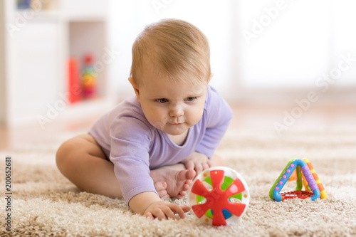 Baby girl playing with colorful toys sitting on a carpet at home - 200652681