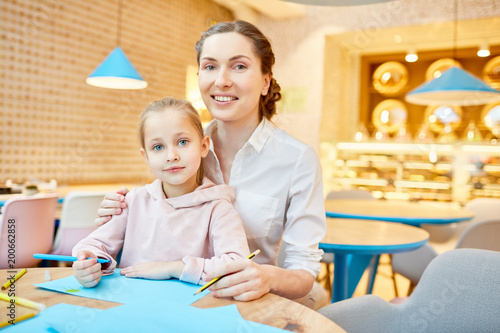 Young woman and little girl with crayons looking at camera while sitting by table in cafe at leisure