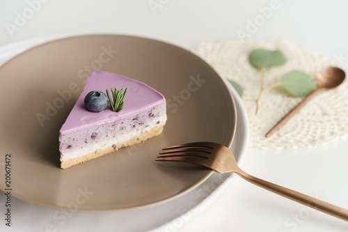 Sticker piece of blueberry cheesecake on brown ceramic plate with fork and spoon on white table