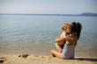Cute little sisters sitting on a beach