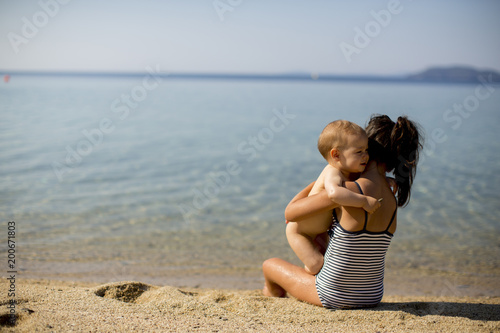 Cute little sisters sitting on a beach