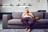 Funny man eating a burger on the couch - 200672009