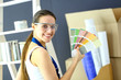 Young woman holding a color swatch with a painter painting