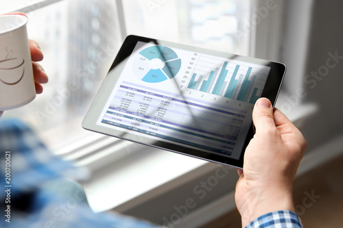 Business man working and analyzing financial figures on a graphs on a tablet in the office