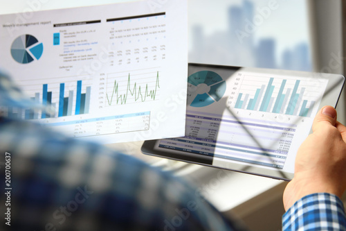 Business man working and analyzing financial figures on a graphs using tablet