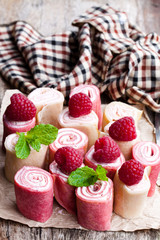 Rolled  milk and raspberry pancakes on wooden table